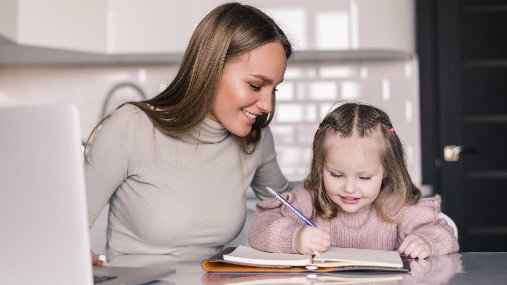 Mujer adulta ayudando a su pequeña hija a hacer tareas