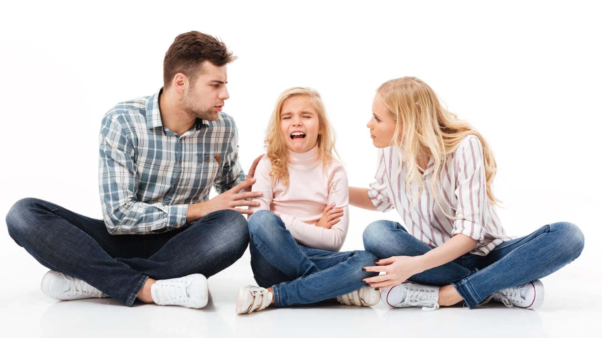 Padre y madre tratando de calmar a su pequeña que hace una rabieta