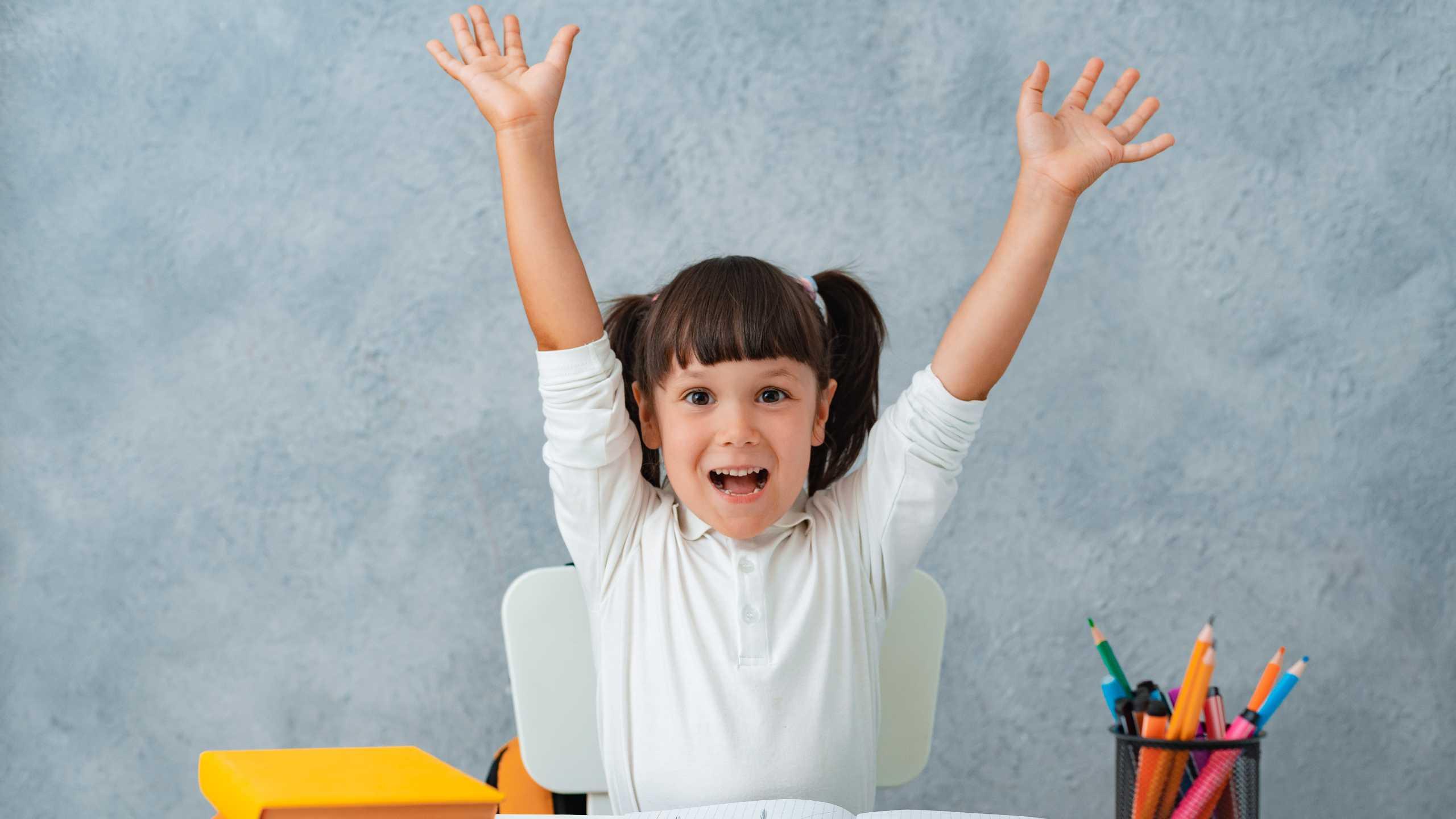 Niña colegiala sentada en un escritorio en una habitación