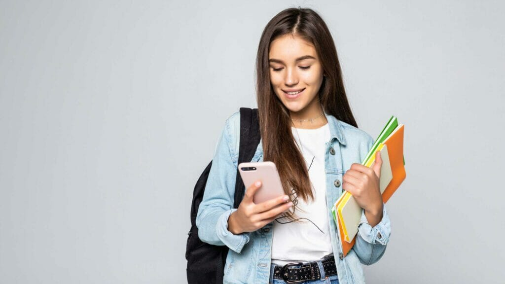 Retrato de mujer joven feliz de pie con mochila con libros y teléfono móvil aislado en la pared blanca