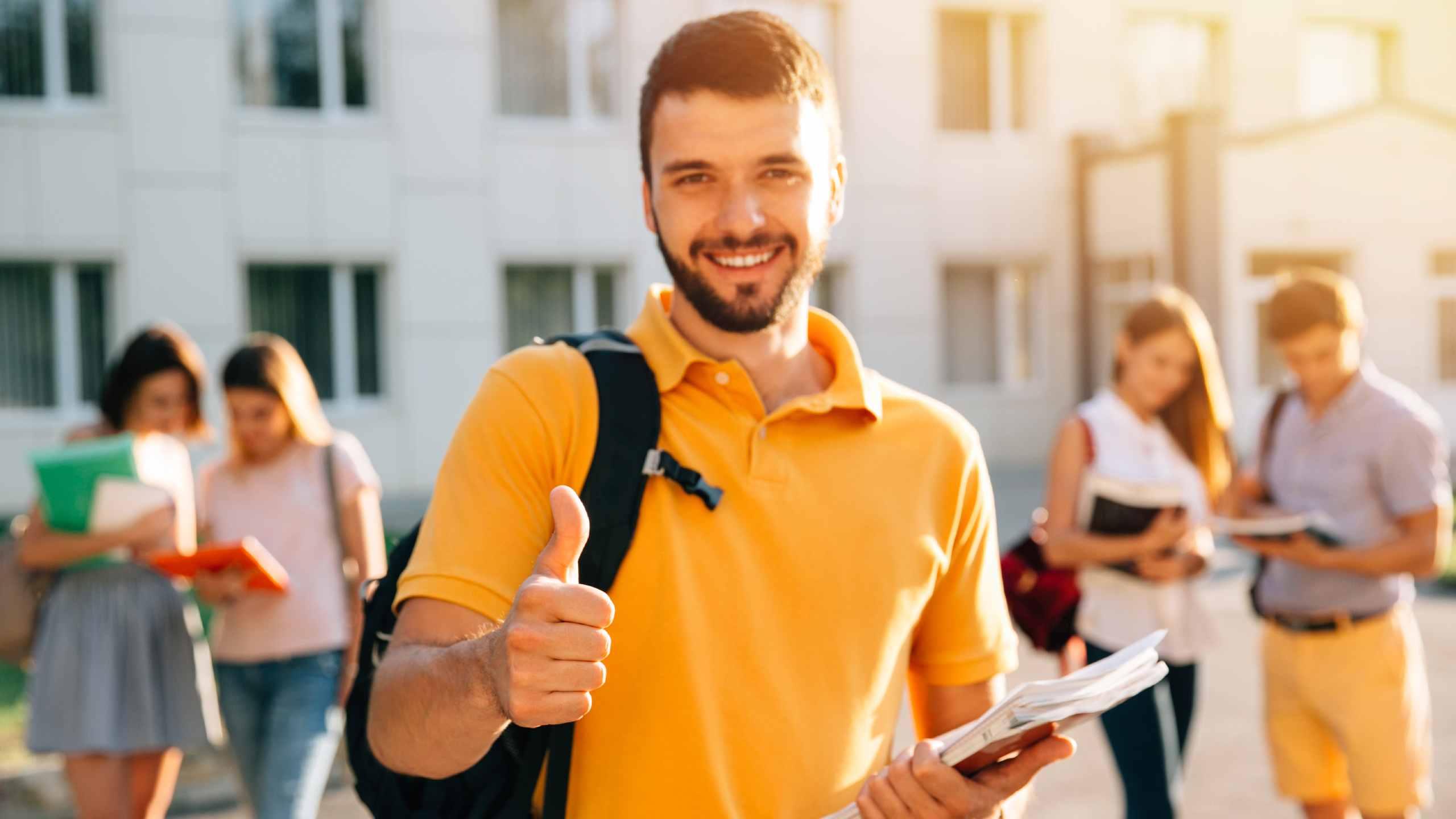Estudiante sonriente atractivo joven que muestra el pulgar para arriba al aire libre en campus en la universidad