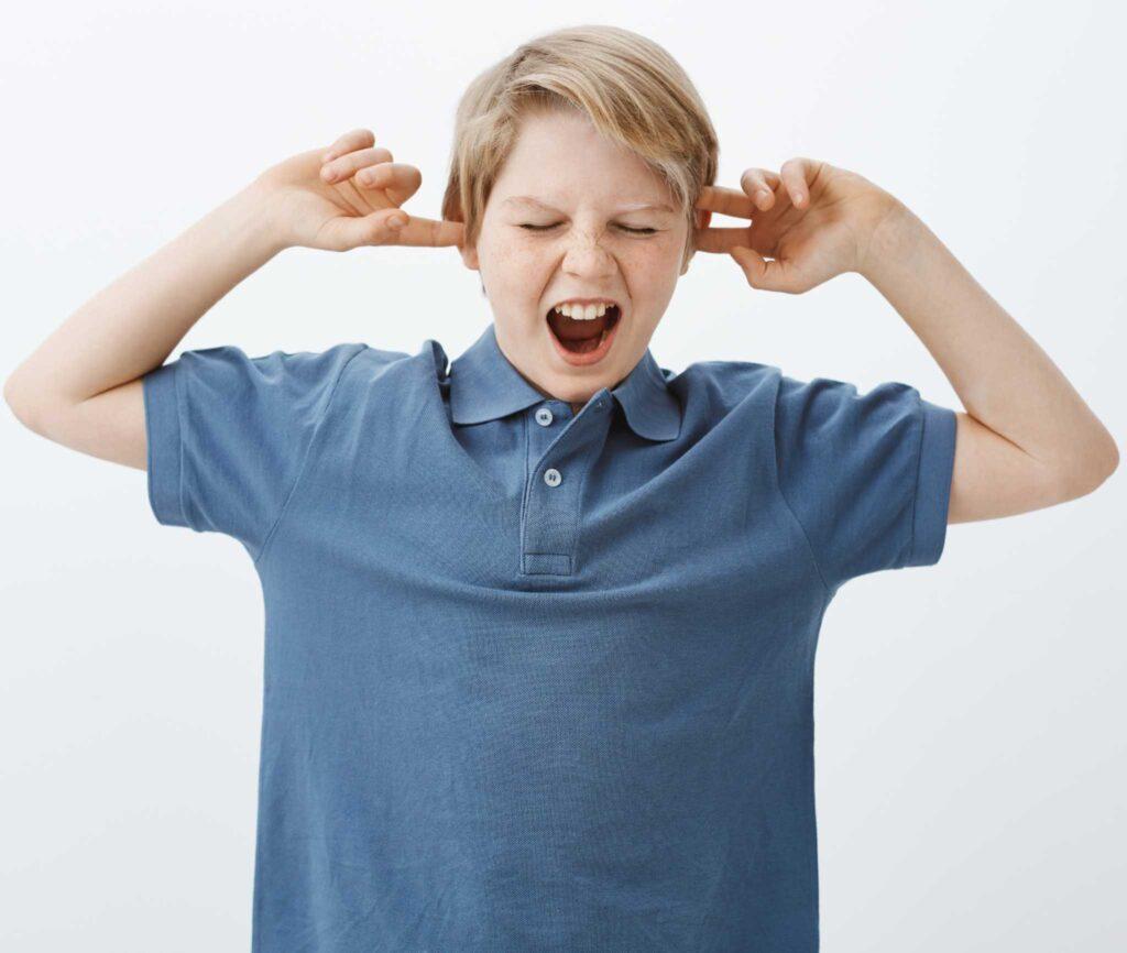 Niño tapándose los oídos con ambas manos mientras grita enojado