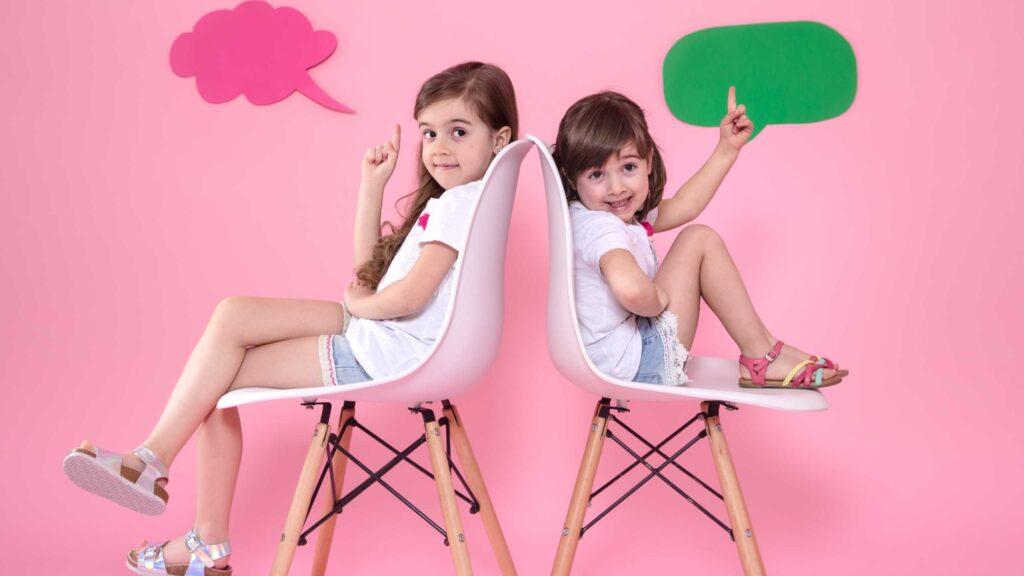 Dos niñas en la pared de color con iconos de voz