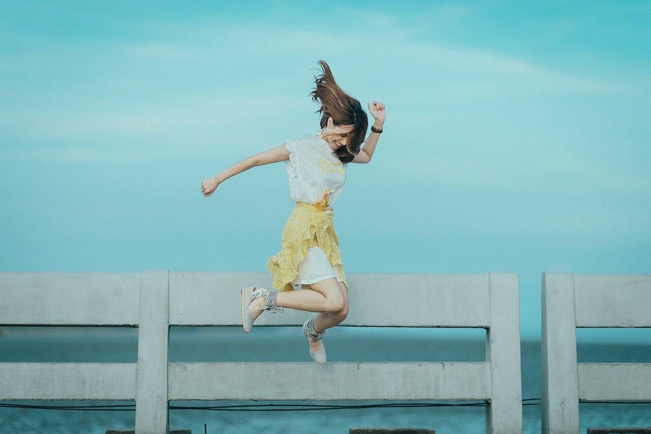 Mujer saltando feliz con el cielo azul de fondo en el muelle