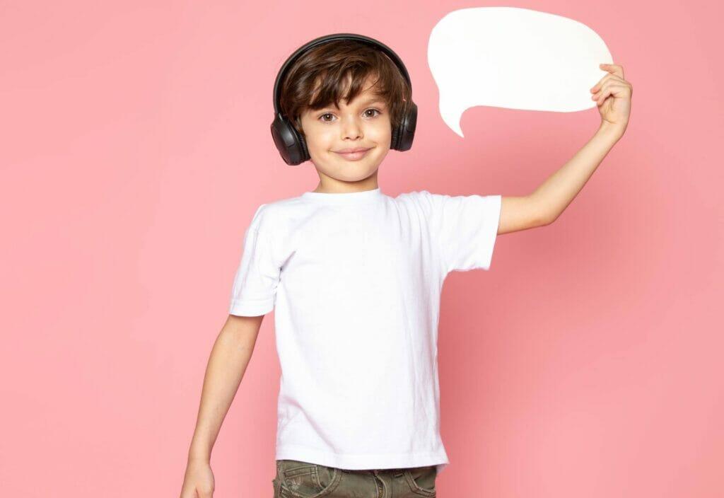 Niño sonriendo mientras sostiene un símbolo de mensaje en su mano con pared de fondo rosada