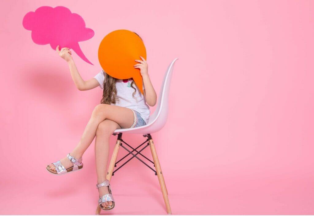 Niña tapando su rostro con carteles de mensajes sentada en una silla y con una pared rosa de fondo
