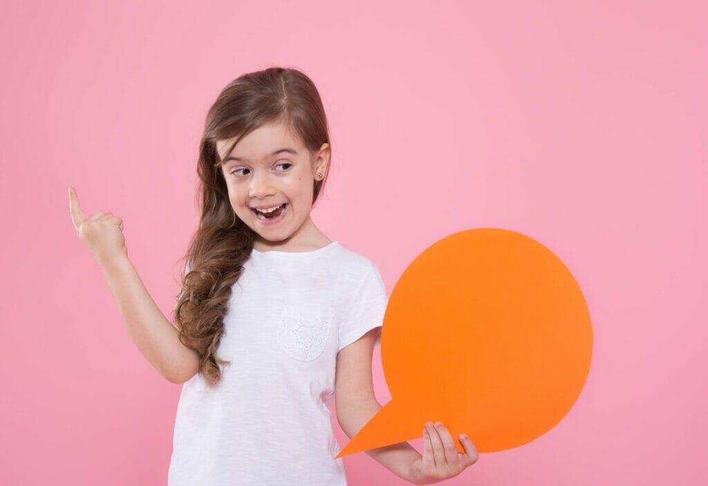 Niña sonriendo sosteniendo símbolo de mensaje en su mano con pared de fondo rosada