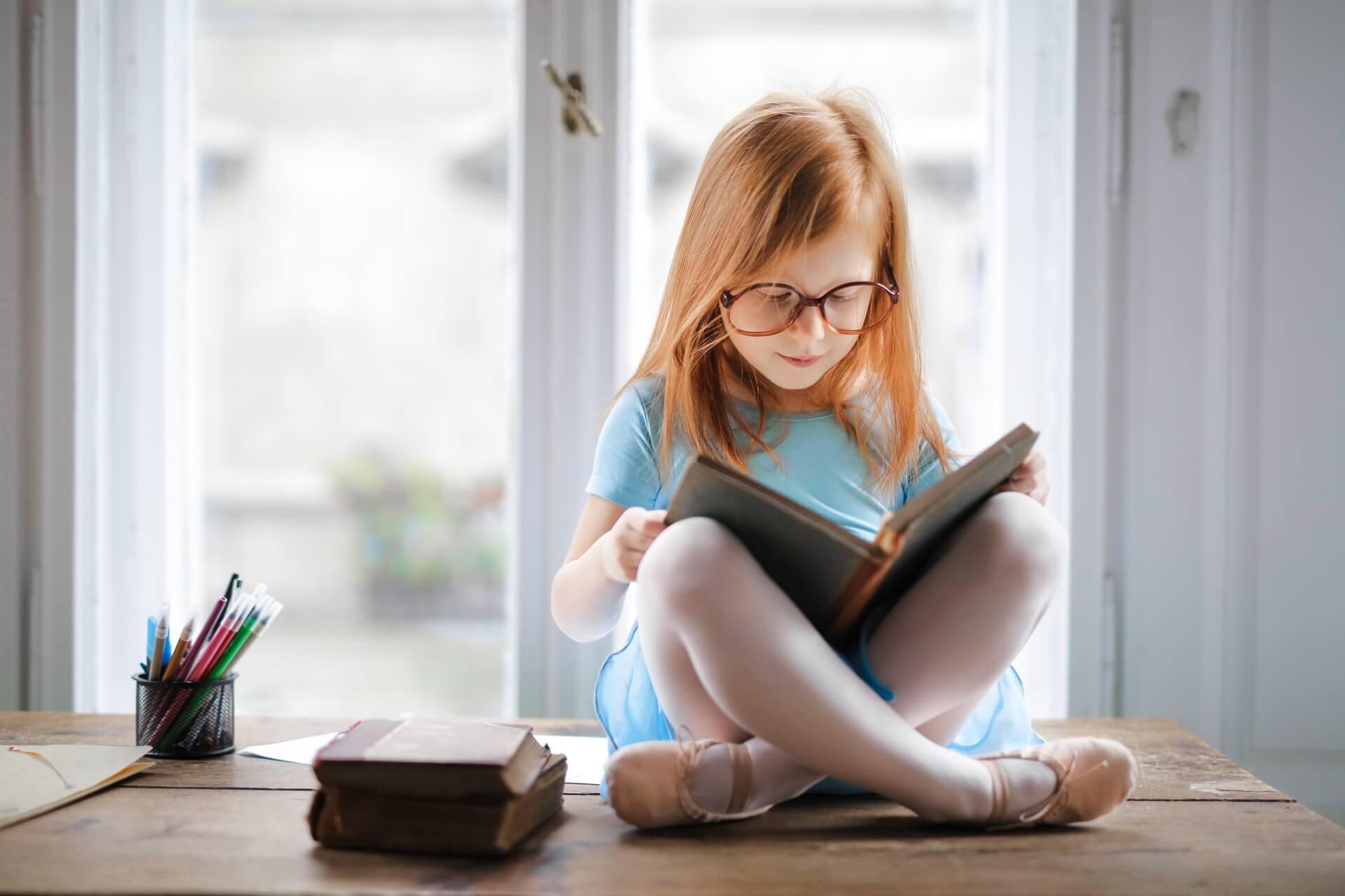 Niña con vestido azúl leyendo un libro sentada en un escritorio con una ventana de fondo