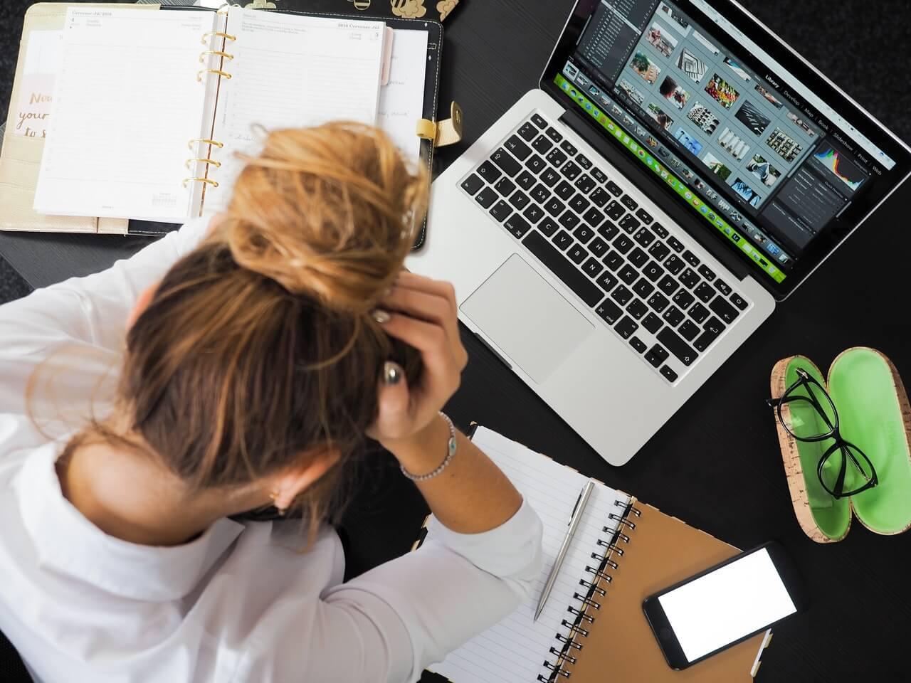 Mujer trabajando en su computador con las manos en la cabeza producto del estrés que siente